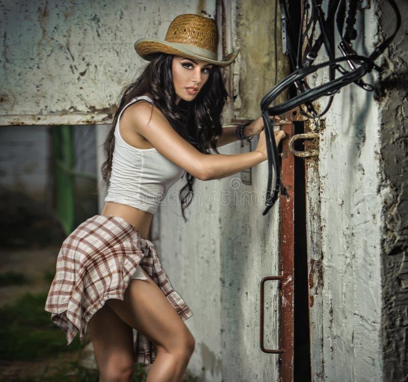 La muchacha morena hermosa con mirada del país, dentro tiró en estilo estable, rústico La mujer atractiva con el sombrero de vaqu foto de archivo