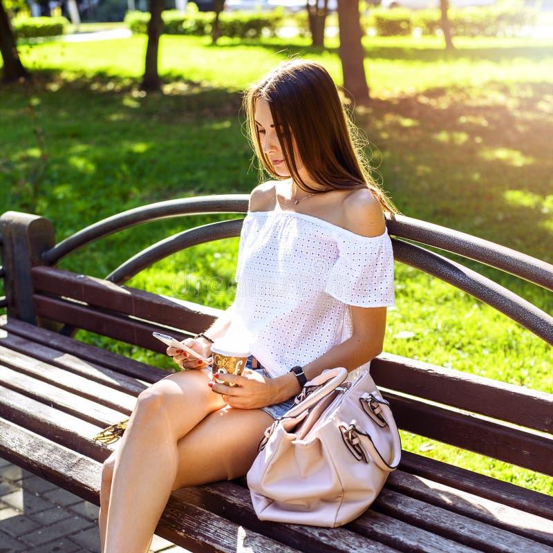 La muchacha morena hermosa que se sienta en un banco en el parque soleado del verano, leyendo la red social, disfruta de sus vaca fotos de archivo libres de regalías