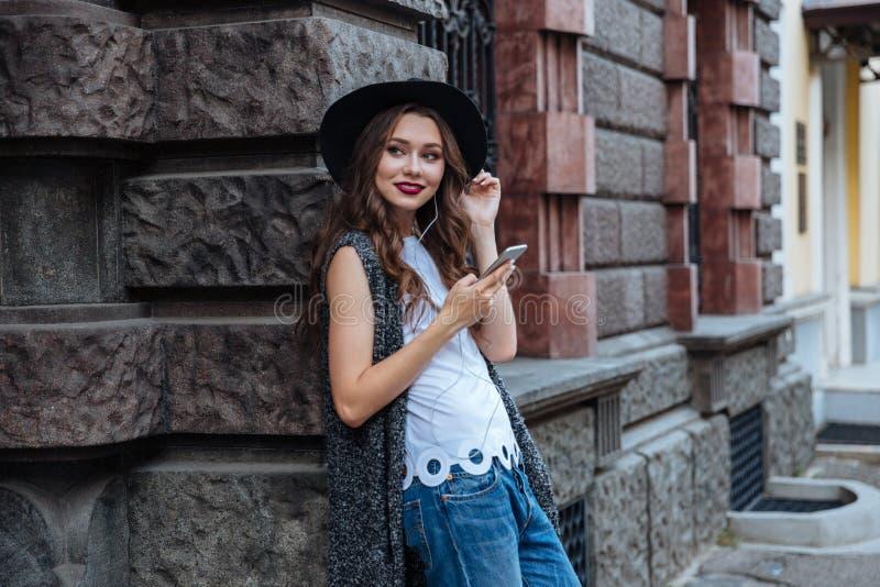 La muchacha morena hermosa sonriente de los jóvenes escucha música con los auriculares al aire libre fotografía de archivo