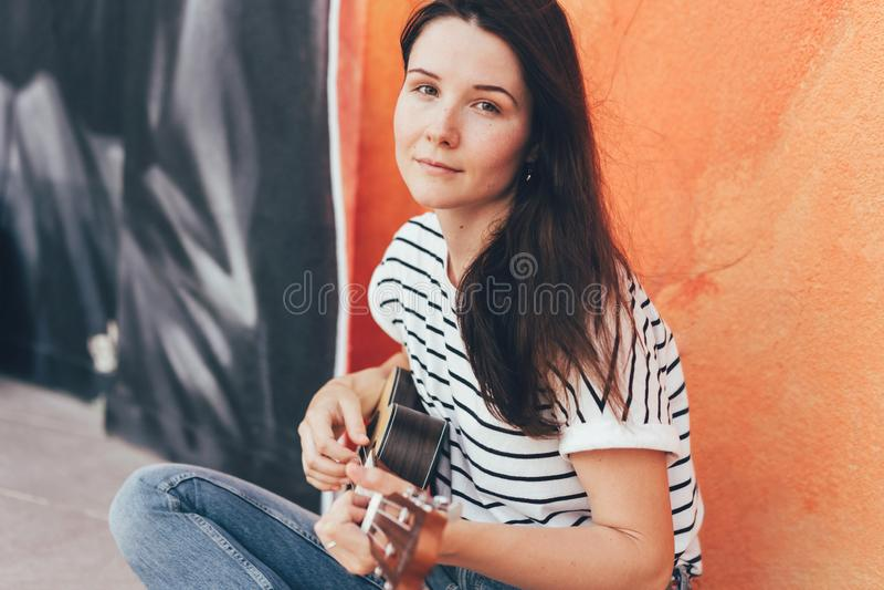 La muchacha morena hermosa toca la guitarra del ukelele imagenes de archivo