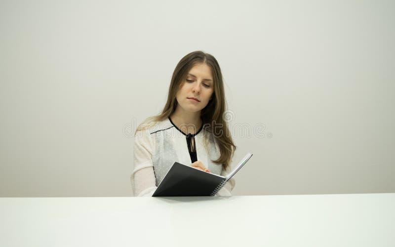 La muchacha morena joven con el pelo que fluye se está sentando en una tabla con un cuaderno en sus manos imagen de archivo libre de regalías
