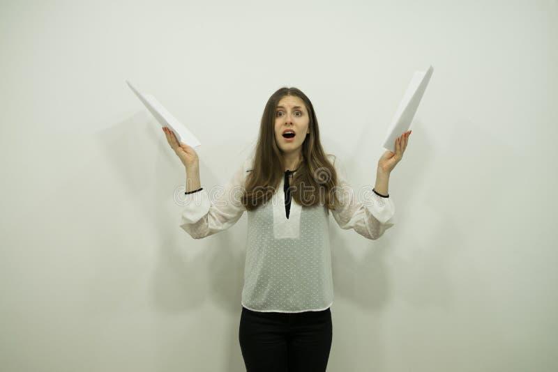 La muchacha morena joven con el pelo que fluye y una boca abierta en choque se está colocando a la derecha que sostiene las hojas imagenes de archivo
