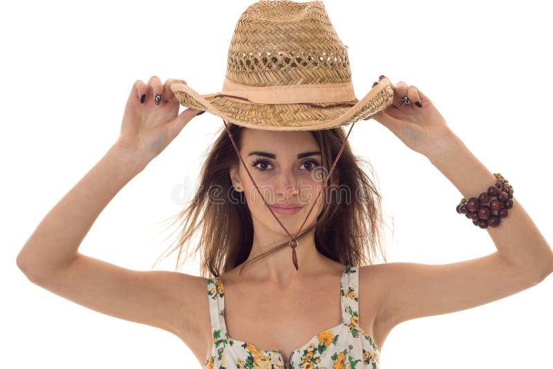 La muchacha morena joven encantadora con el sombrero y el verano de paja viste con el estampado de flores que mira la cámara aisl foto de archivo libre de regalías