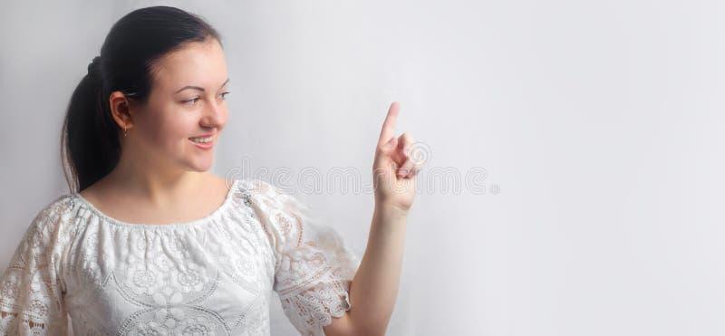 La muchacha morena joven hermosa señala el finger en el espacio de la copia en fondo blanco aislado lugar de la información impor imagen de archivo