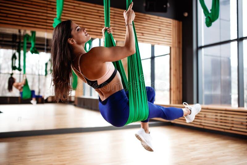 La muchacha morena joven hermosa vestida en la ropa del deporte está haciendo aptitud en la seda aérea verde en el gimnasio imagen de archivo libre de regalías