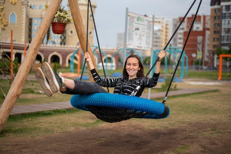 La muchacha morena que balancea en un oscilación de la ejecución en el parque que sonríe con el placer, concepto de libertad, día imagenes de archivo