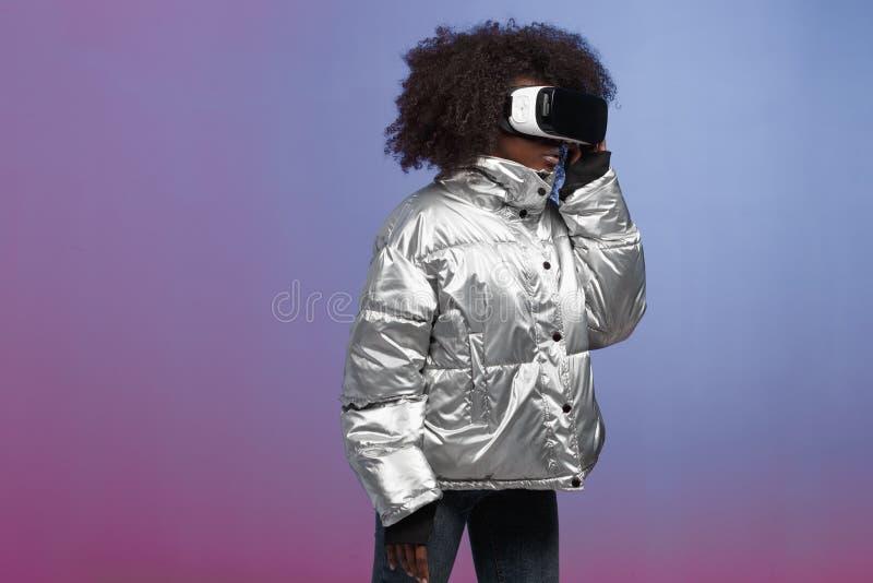 La muchacha morena rizada de moda vestida en una chaqueta plata-coloreada utiliza los vidrios de la realidad virtual en el estudi imagen de archivo