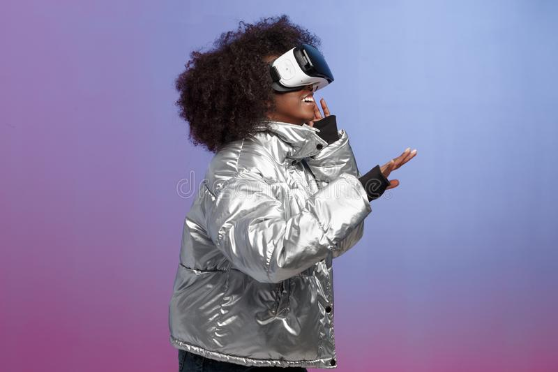 La muchacha morena rizada de moda vestida en una chaqueta plata-coloreada utiliza los vidrios de la realidad virtual en el estudi fotografía de archivo