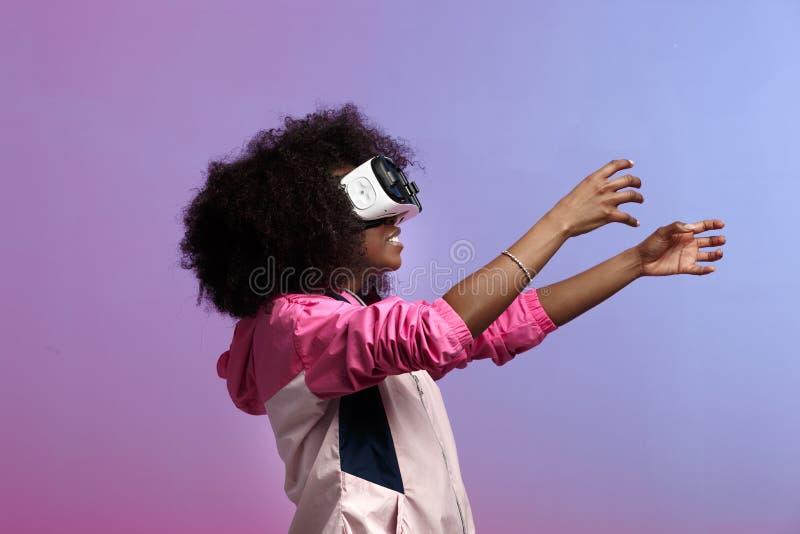 La muchacha morena rizada moderna vestida en la chaqueta de deportes rosada utiliza los vidrios de la realidad virtual en el estu fotos de archivo libres de regalías