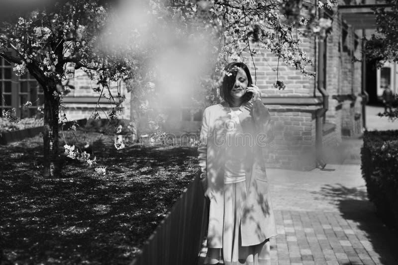 La muchacha morena sonriente hermosa con el pelo corto en ropa ligera está en un jardín florido de la primavera con un cerezo Los fotos de archivo libres de regalías