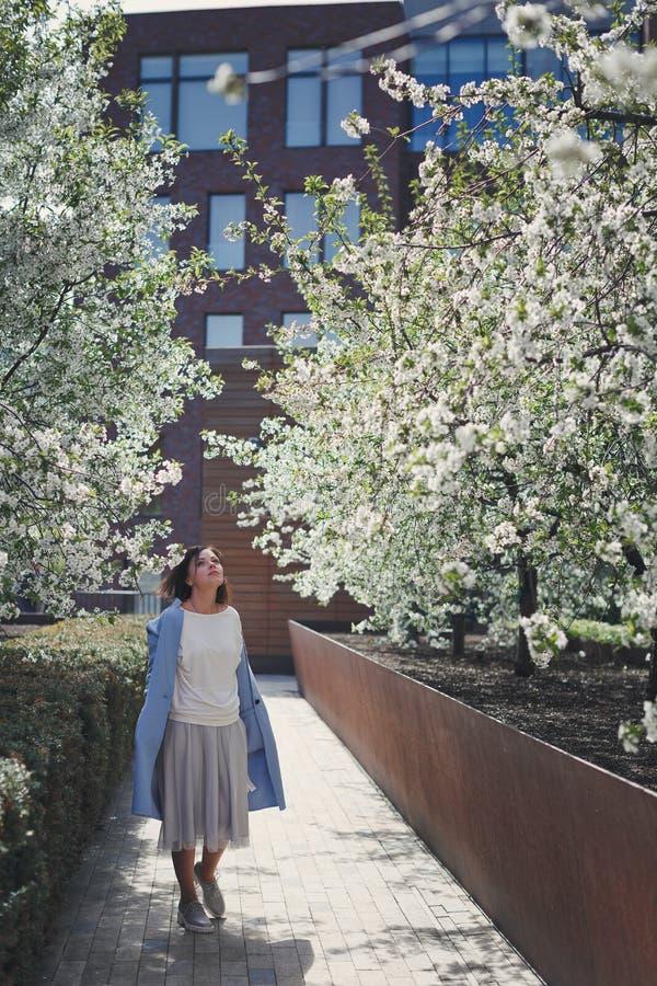 La muchacha morena sonriente hermosa con el pelo corto en una capa azul está en un jardín florido de la primavera con un cerezo L foto de archivo libre de regalías