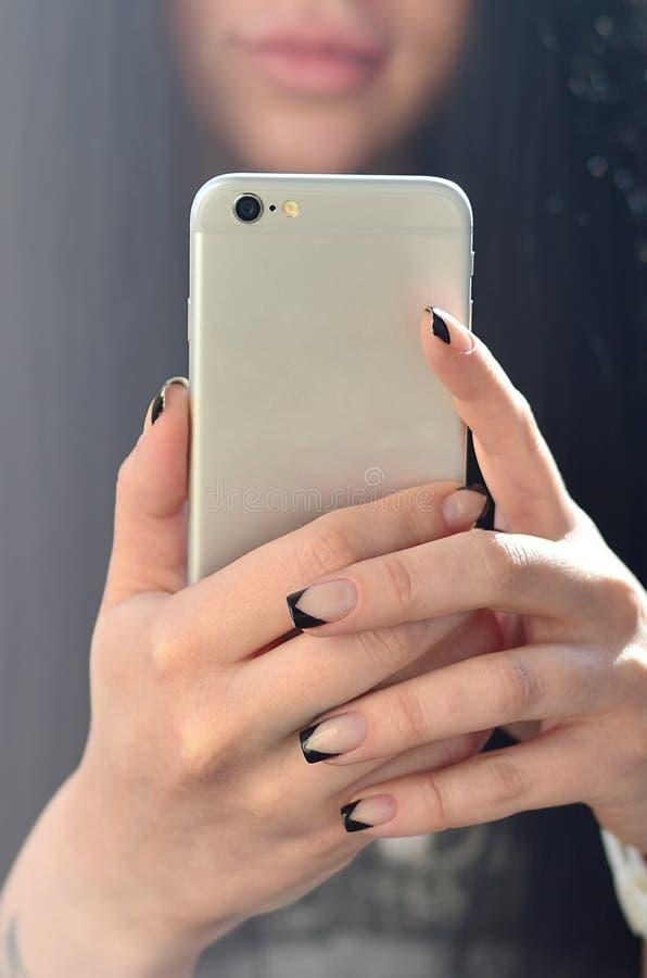 La muchacha morena toma el selfie en un smartphone moderno del tacto fotografía de archivo libre de regalías
