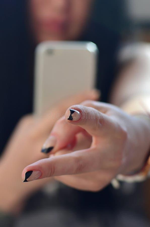 La muchacha morena toma las imágenes de sus dos fingeres en un moderno fotos de archivo