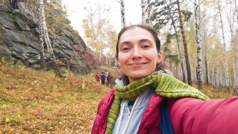 La muchacha morena toma un selfie durante un alza del grupo en el bosque en la estación fría Caliente-chaqueta vestida, bufanda fotos de archivo libres de regalías