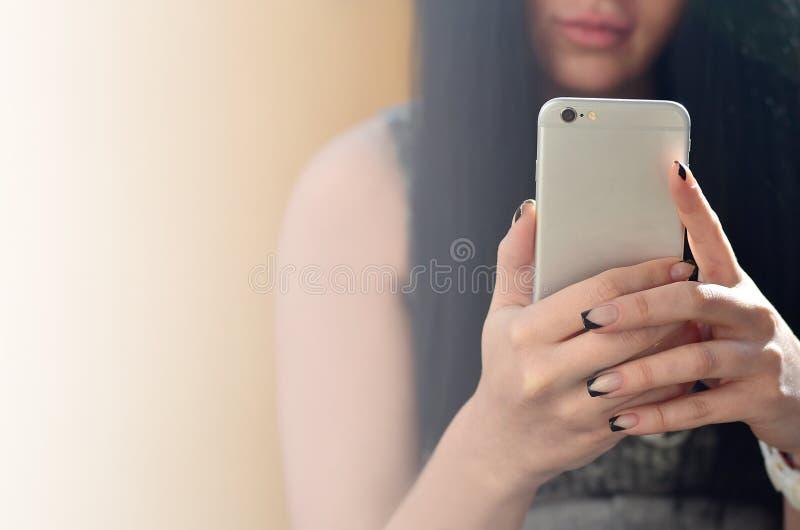 La muchacha morena utiliza un smartphone moderno del tacto imágenes de archivo libres de regalías