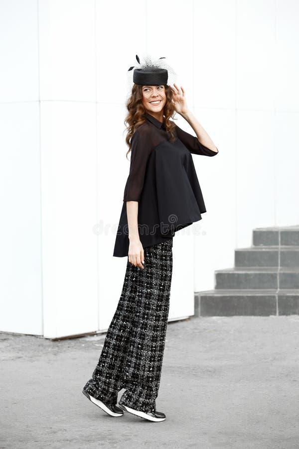 La muchacha morena vestida en una camisa negra elegante, se?al? por medio de luces los pantalones y el peque?o sombrero de moda p foto de archivo