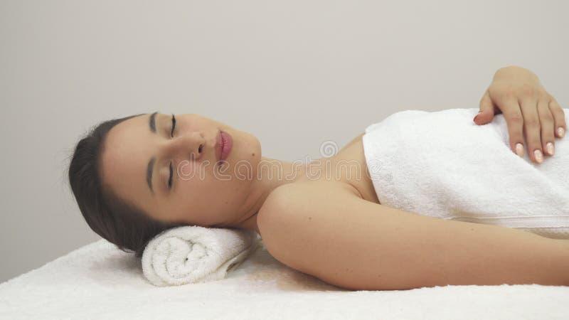 La muchacha muestra su pulgar para arriba en la tabla del masaje fotos de archivo libres de regalías