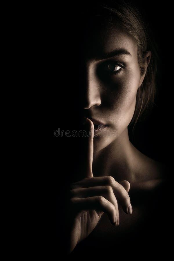 La muchacha muestra una muestra del silencio Cara en fondo negro imagen de archivo
