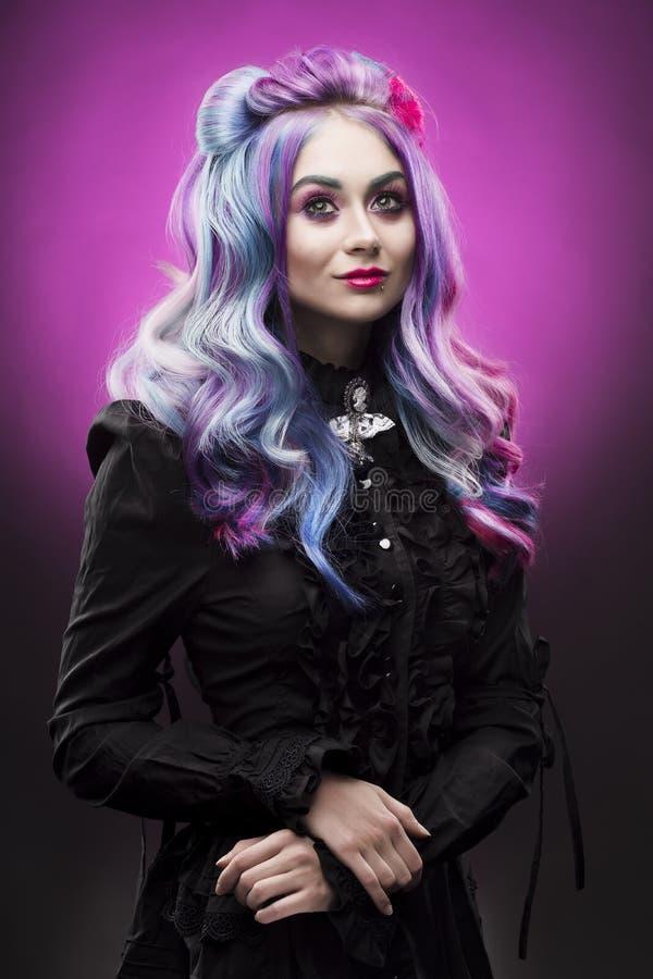La muchacha multicolora gótica del pelo en un fondo violeta fotografía de archivo