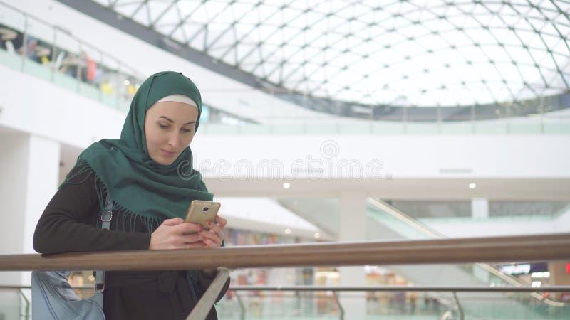 La muchacha musulmán hermosa en hijab utiliza smartphone en centro de negocios moderno imágenes de archivo libres de regalías