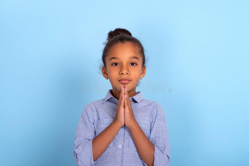La muchacha muy rizada del mulatta joven ruega contra un fondo azul con el espacio de la copia imagen de archivo