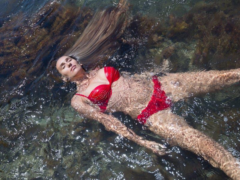La muchacha nada en la parte posterior en el mar foto de archivo libre de regalías
