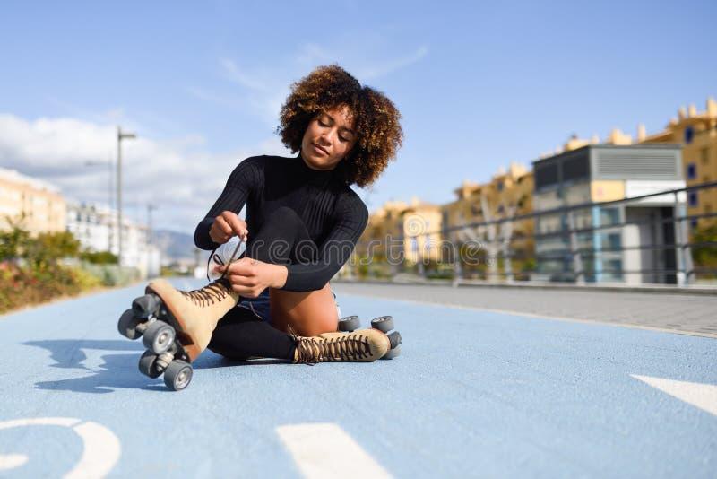 La muchacha negra sonriente de los jóvenes que se sienta en línea de la bici y pone patines fotos de archivo
