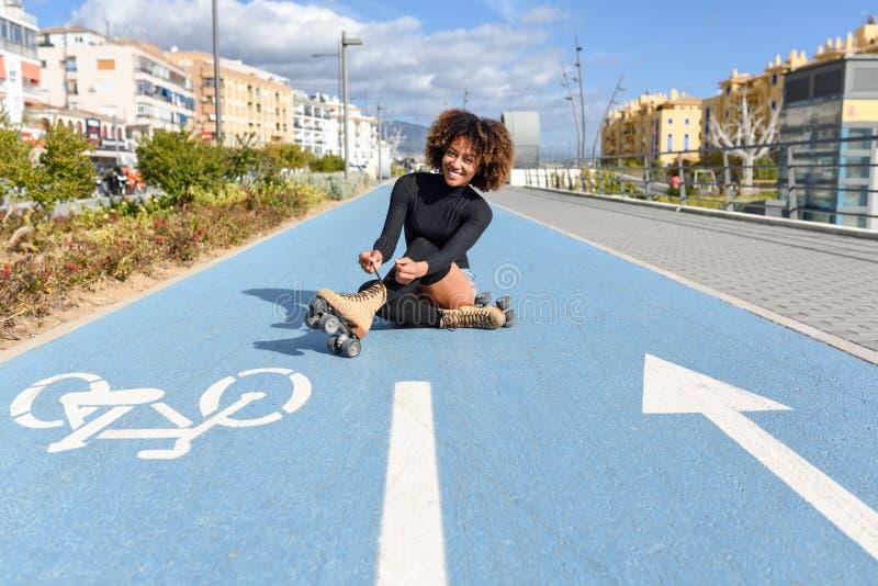 La muchacha negra sonriente de los jóvenes que se sienta en línea de la bici y pone patines imagen de archivo libre de regalías