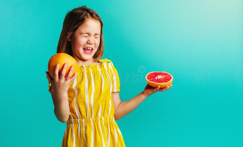 La muchacha no le gusta el gusto del pomelo fotografía de archivo