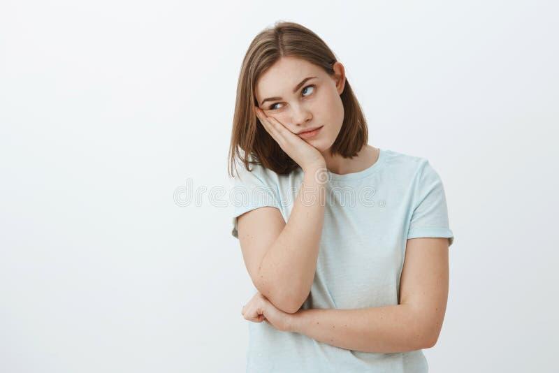La muchacha odia asistir a clases aburridas en la cara que se inclina de la universidad a mano que rueda ojos de la situación del fotografía de archivo