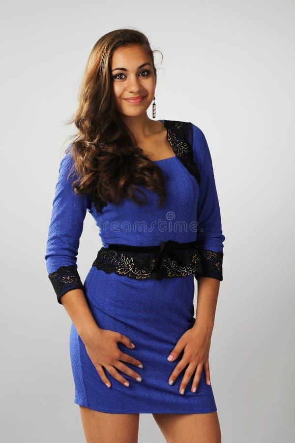 La muchacha oscura con el pelo rizado en un vestido azul imagen de archivo libre de regalías