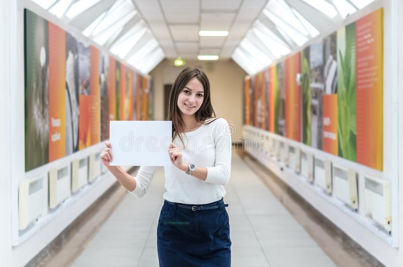 La muchacha oscuro-cabelluda del estudiante en el campus está sosteniendo una hoja de papel en blanco fotos de archivo libres de regalías