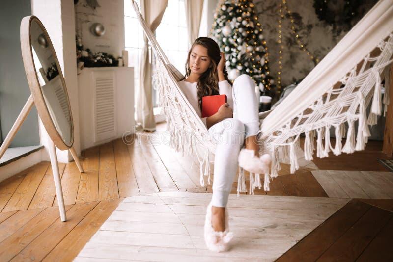 La muchacha oscuro-cabelluda hermosa vestida en pantalones, su?ter y deslizadores calientes lee un libro que miente en una hamaca foto de archivo libre de regalías