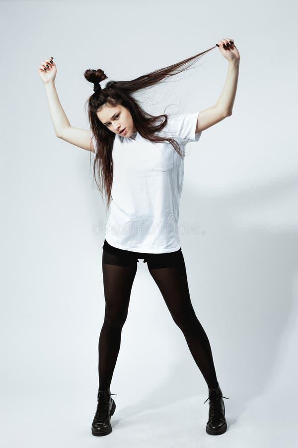 La muchacha oscuro-cabelluda joven elegante con un peinado divertido vestido en la camiseta blanca, medias negras y zapatos está  imagen de archivo