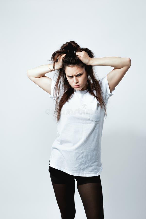 La muchacha oscuro-cabelluda joven elegante con un peinado divertido vestido en la camiseta blanca, medias negras y zapatos está  fotos de archivo