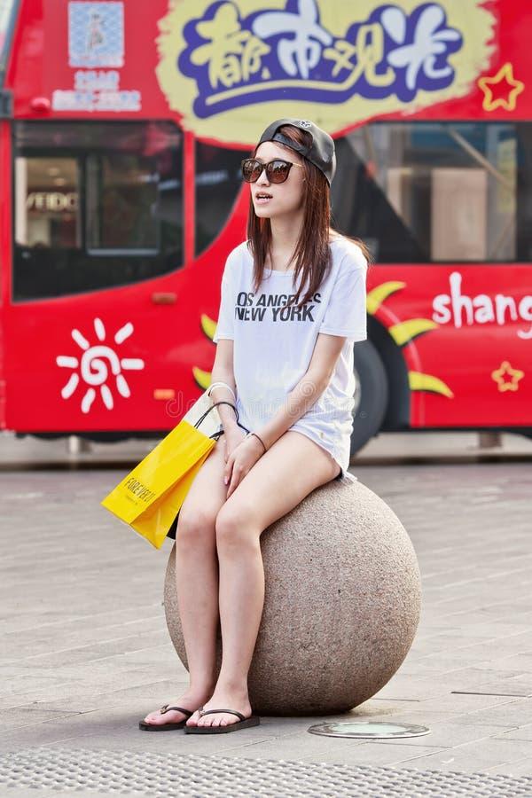 La muchacha pálida de la piel se sienta en la bola concreta, Shangai, China imagenes de archivo