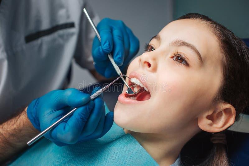 La muchacha pacífica tranquila se sienta en silla dental en sitio Ella mantiene la boca abierta Herramientas del uso del dentista imagen de archivo