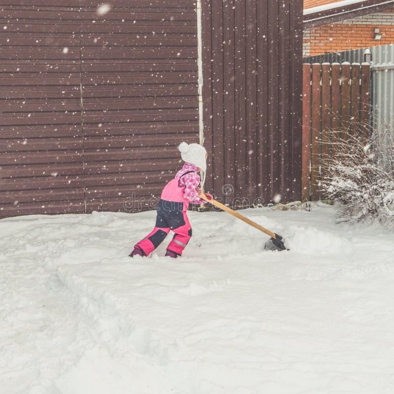 La muchacha, pala grande del bebé quita nieve de la trayectoria en el patio trasero en el garaje fotografía de archivo