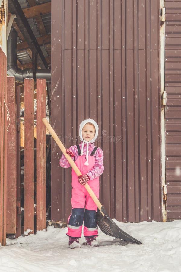 La muchacha, pala grande del bebé quita nieve de la trayectoria en el patio trasero en el garaje imagen de archivo