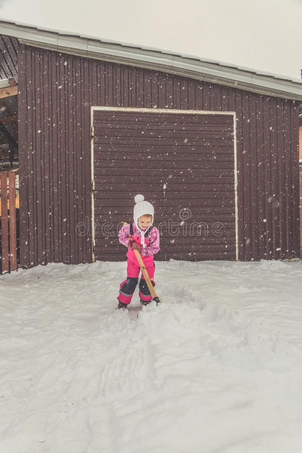 La muchacha, pala grande del bebé quita nieve de la trayectoria en el patio trasero en el garaje fotografía de archivo libre de regalías