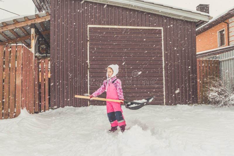 La muchacha, pala grande del bebé quita nieve de la trayectoria en el patio trasero en el garaje imágenes de archivo libres de regalías