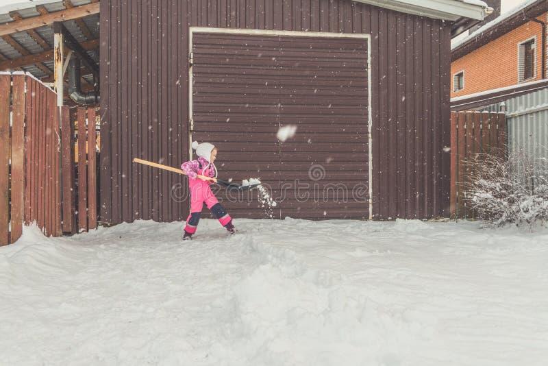 La muchacha, pala grande del bebé quita nieve de la trayectoria en el patio trasero en el garaje fotos de archivo libres de regalías