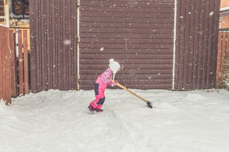 La muchacha, pala grande del bebé quita nieve de la trayectoria en el patio trasero en el garaje foto de archivo libre de regalías