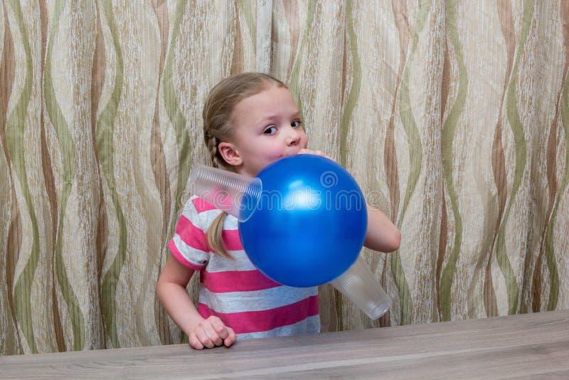 La muchacha pasa experiencia física con el globo y los vidrios imagenes de archivo
