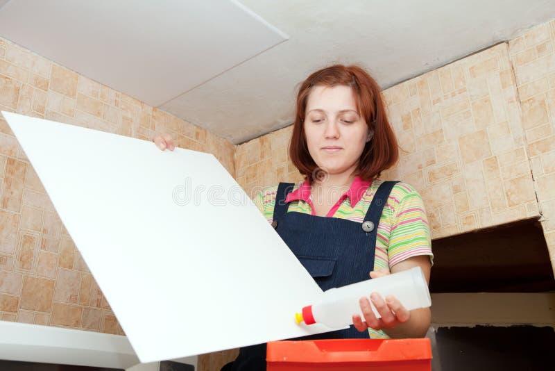 La muchacha pega el azulejo del techo imagen de archivo