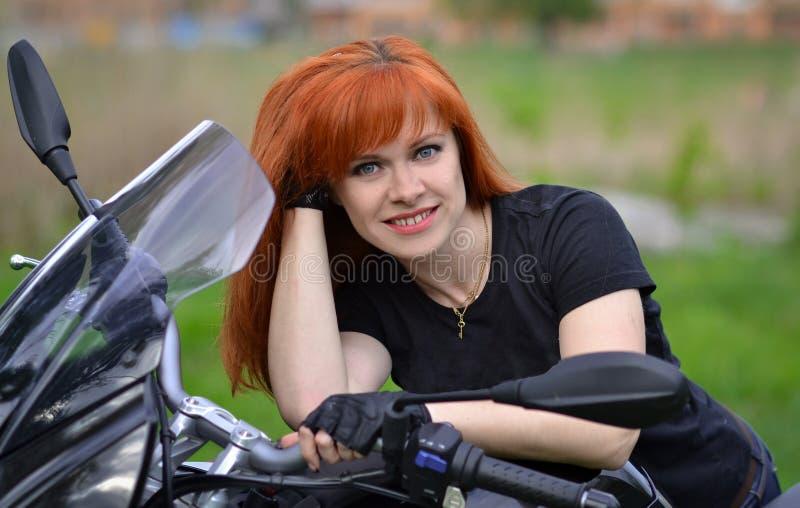 La muchacha pelirroja con sonrisa linda, hermosa se sienta en la moto grande, negra El motorista profesional con los guantes negr imagen de archivo