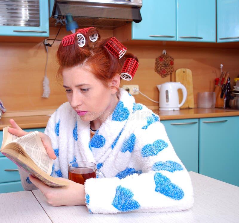 La muchacha pelirroja en una bata en cocina hiere los bigudíes de pelo, negro dirigido al té y sentado para leer la novela fotos de archivo