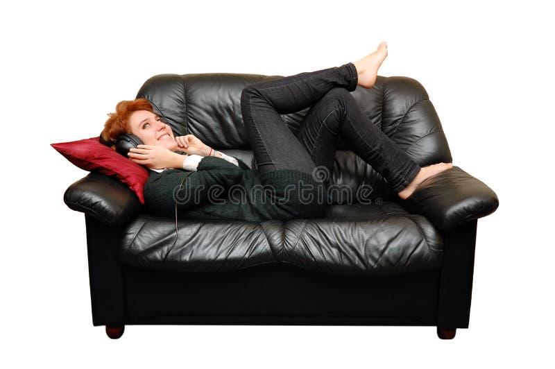 La muchacha pelirroja está poniendo en el sofá fotografía de archivo