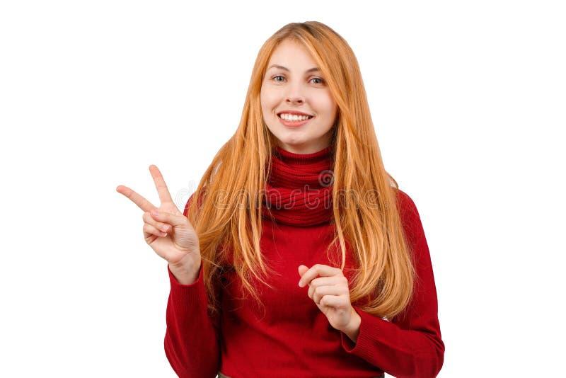 La muchacha pelirroja feliz está sonriendo y muestra a gesto dos pulgares para arriba En el fondo blanco fotos de archivo libres de regalías