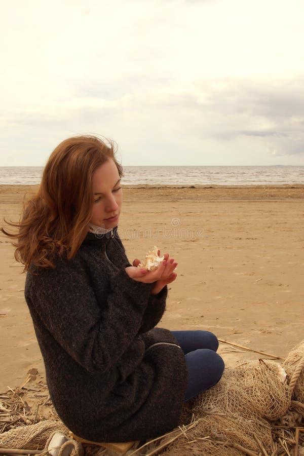 La muchacha pelirroja joven se sienta en una red de pesca y mira una concha marina en sus manos fotos de archivo